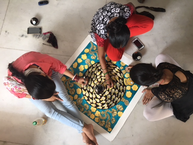 Aerial view of three artisans work together on a painting