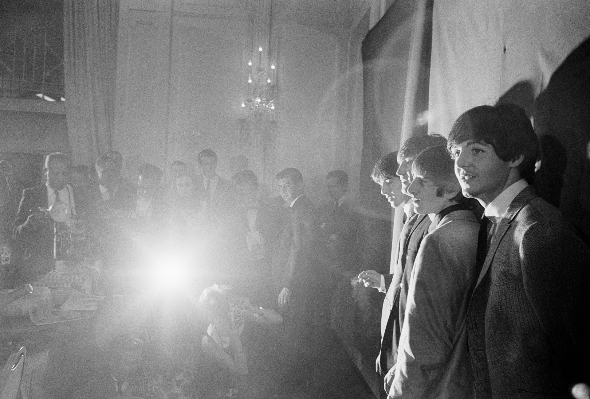 Black and white photograph of The Beatles standing against a white backdrop as a crowd looks on.