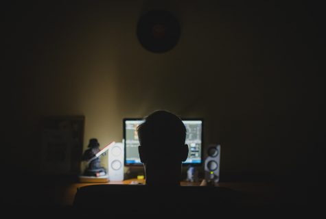 man in the dark illuminated by computer light