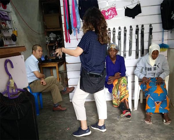 Devon Hsiao conducting interviews in a retail space in Kampala, Uganda.