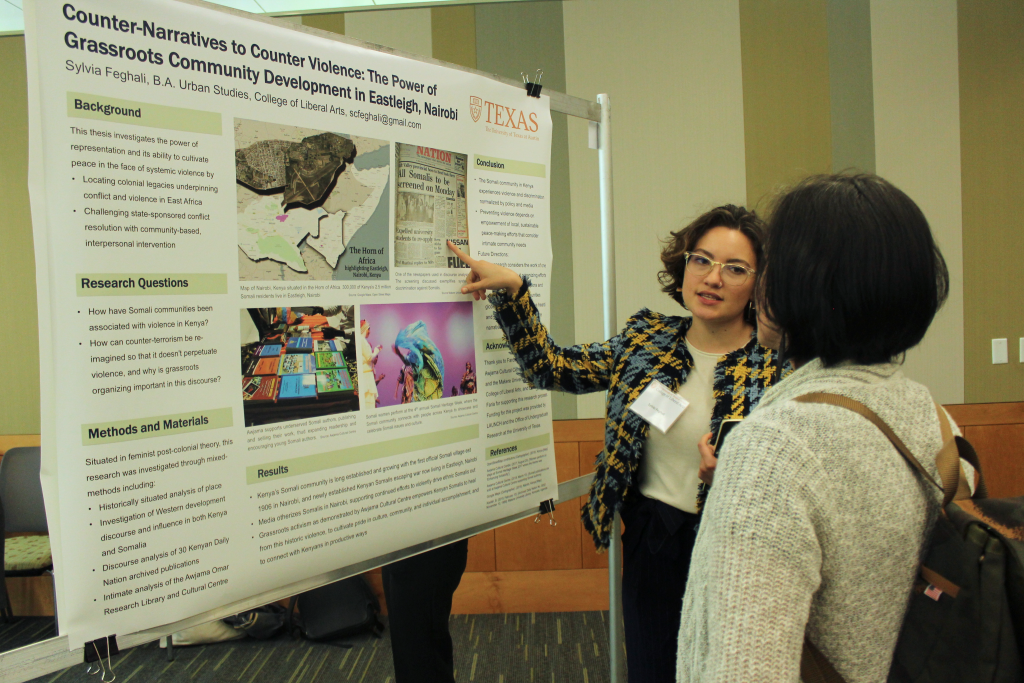 Sylvia Feghali points to her research poster while speaking to a woman.