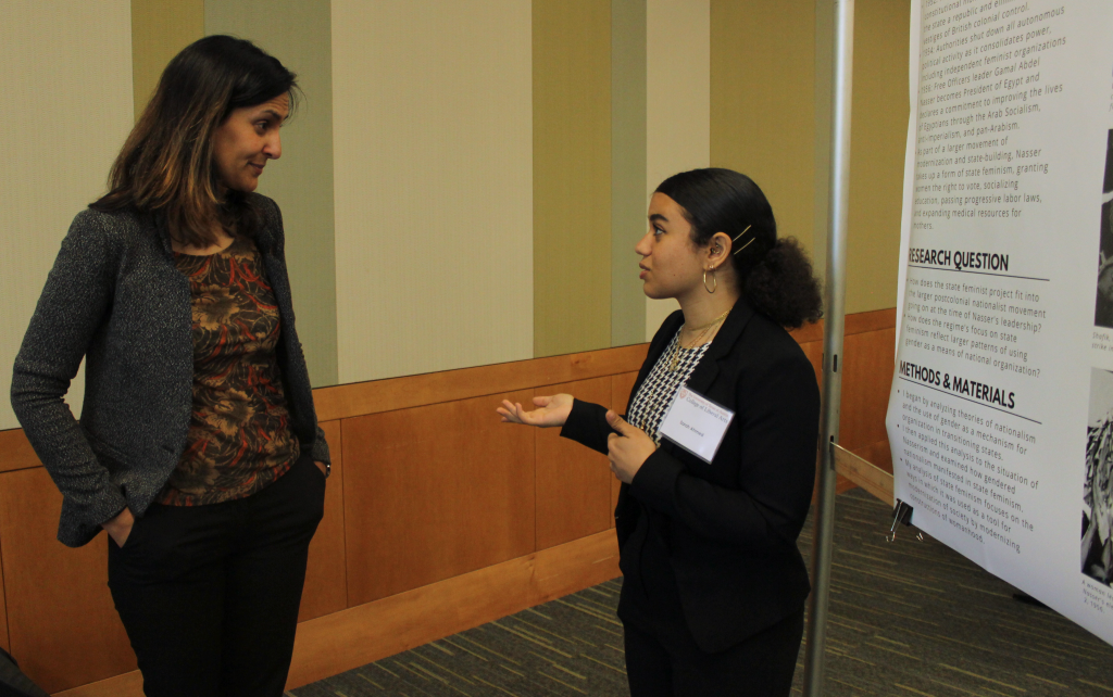 Sarah Ahmed stands in front of her research poster explaining her research.