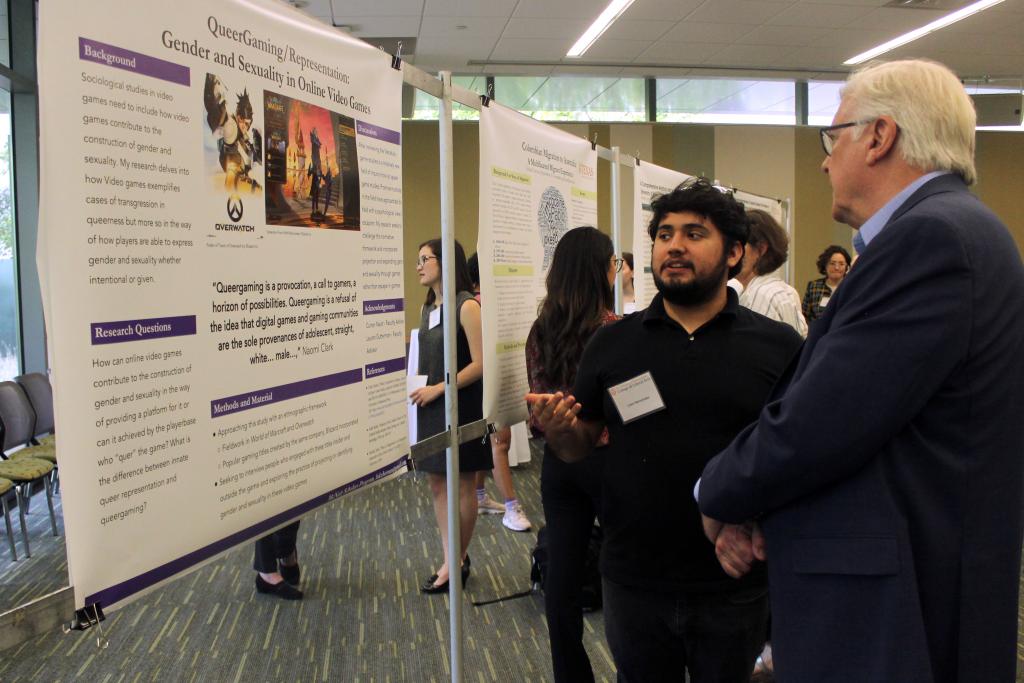 Luke Hernandez  explains his research poster to Randy Diehl.