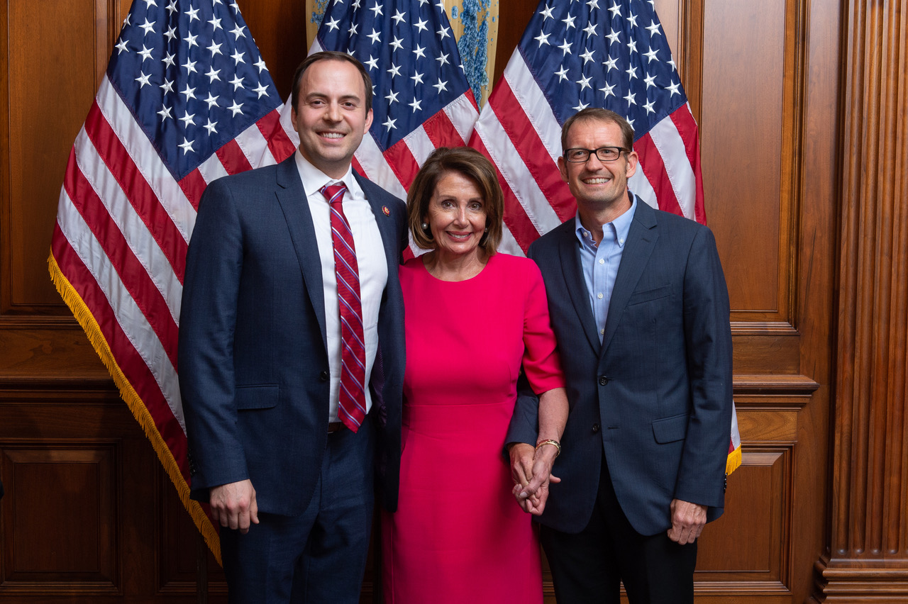 Rep. Lance Gooden, Speaker Nancy Pelosi, and Professor Sean Theriault during Gooden's swearing-in ceremony with three American flags and wooden panel walls as background.