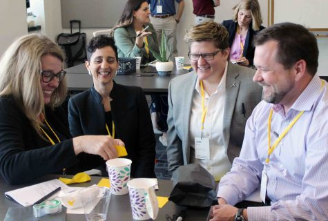 A group of four people with yellow lanyards around their necks laughing and working together during a Design Thinking workshop.