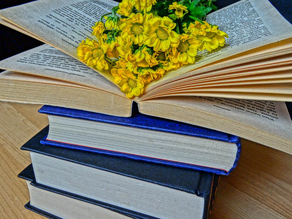Stack of books. Top book is open with yellow flowers in center.