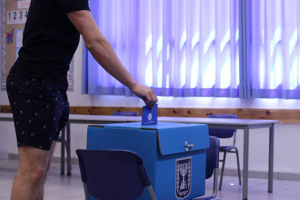 Man casting his vote in blue box located on folding chair with sheer lavender curtains as background.