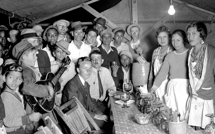 An old photo of a group of people standing around a table