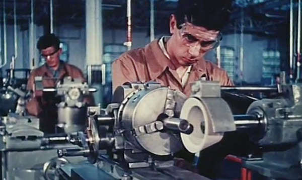 A machine shop worker using tools