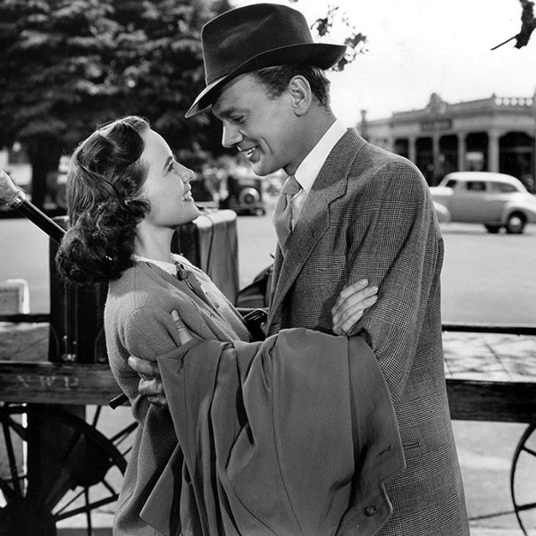 A black and white still from a movie with a man and woman closely talking