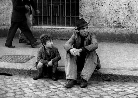 Black and white photo of a man and young boy sitting on a sidewalk