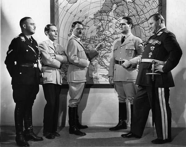 A black and white still showing Nazis gathered around a map of Europe