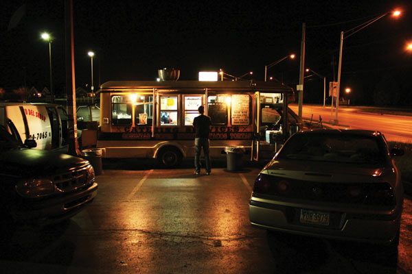 A man standing outside a taco truck at night.