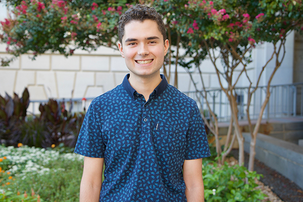 Isaac James smiles happily in front of a flower bed with a variety of plants, wearing a patterned blue shirt.