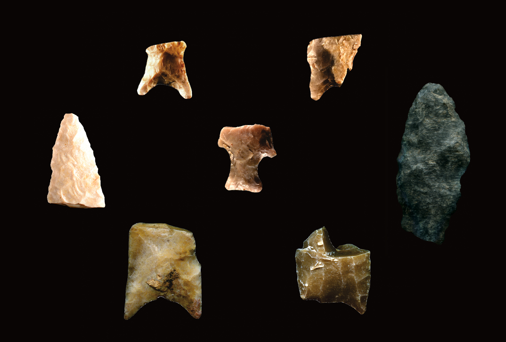 various pieces of arrowheads made of stone on a black background with a scale of 0-2cm at the bottom