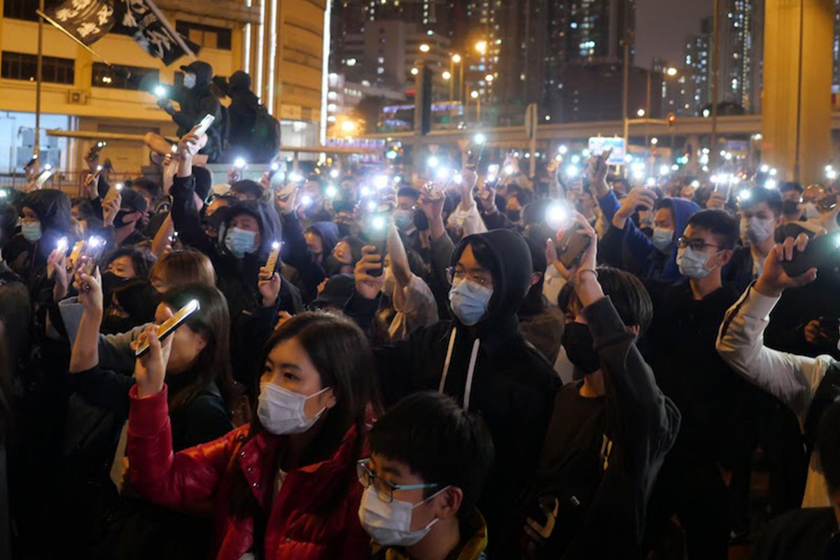 protesters holding up phones as flashlights