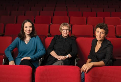 Three women sitting in an empty movie theater