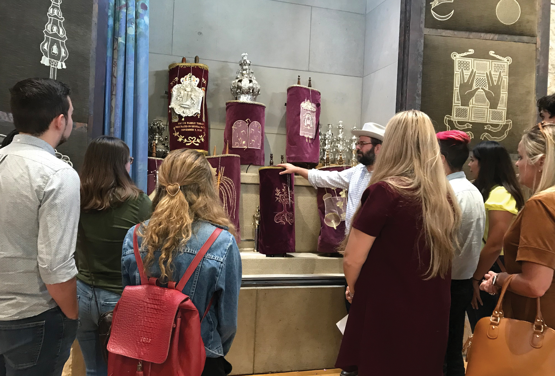 A group gathered around a collection of royal crowns and artifacts