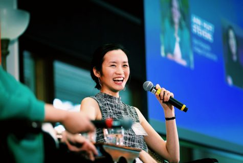 Margaret Siu sits in a chair while holding a microphone up to her mouth. She is laughing happily at what is clearly a public speaking event.