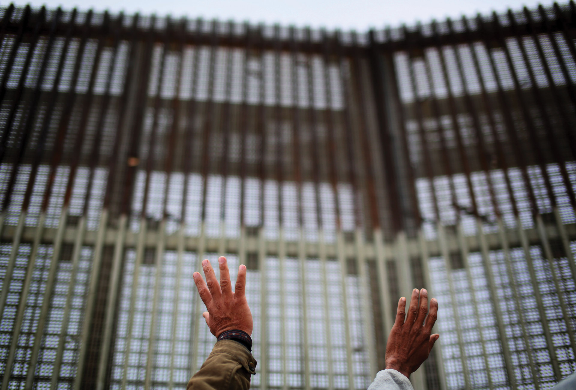 Photo of two outstretched hands in front of a large, imposing border fence.