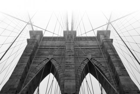 Black and white photo of the Brooklyn Bridge shrouded in a white fog.