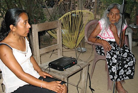 A young woman speaking to an elderly woman. The older woman speaks into a microphone recorder.