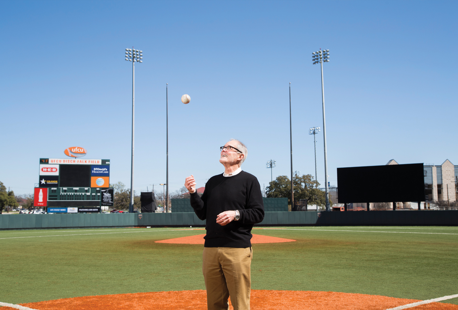 Larry Carver stands on the pitcher's mound of the UFCU Disch-Faulk field and tosses a baseball up in the air.