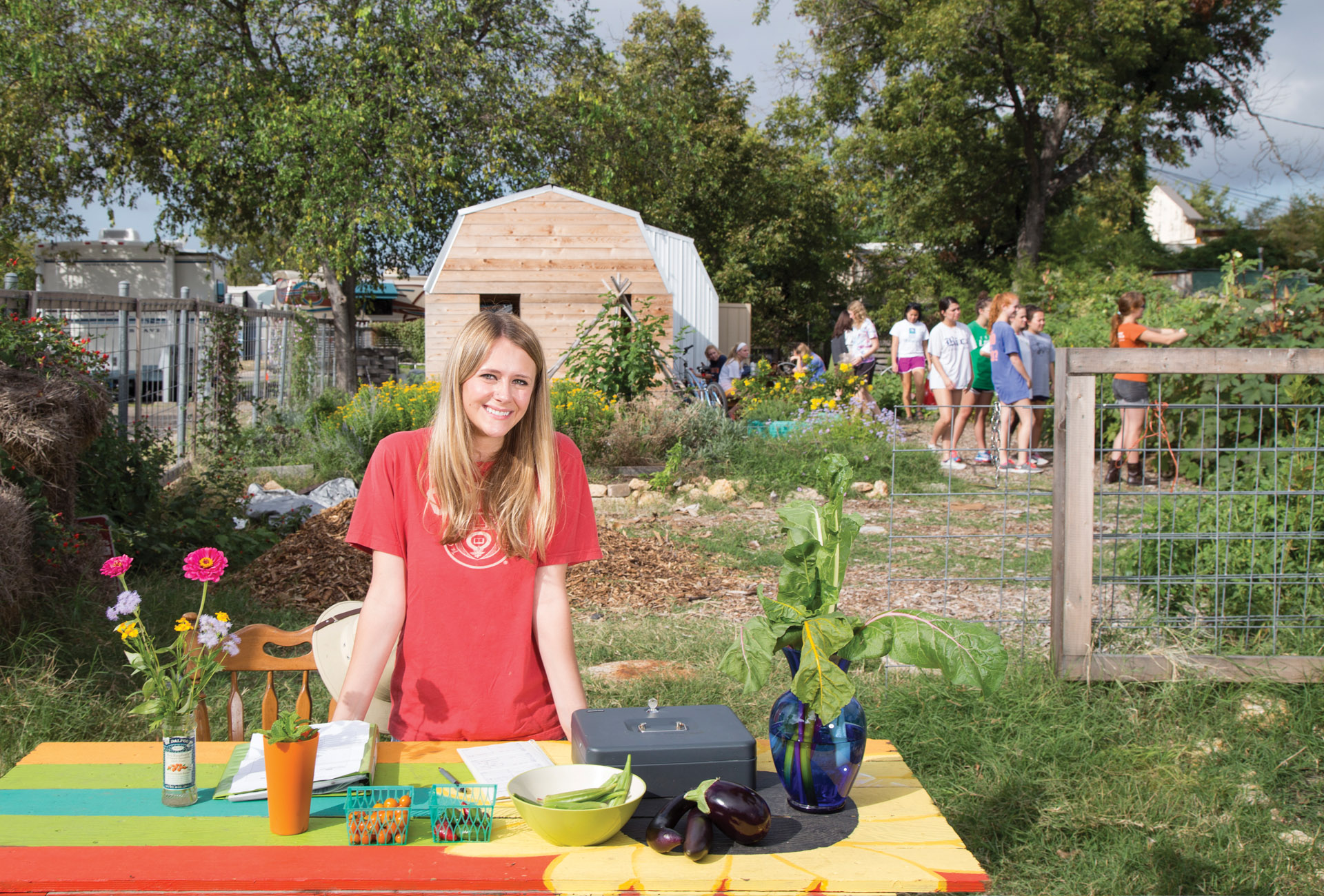 Photo of community garden with a smiling woman at the vegetable stand. A large shed is in the background along with a group of students being shown how to harvest vegetables.