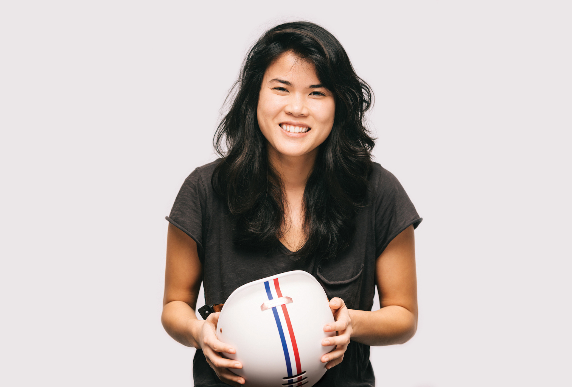 Portrait of Gloria Hwang holding a Thousand stripped helmet.