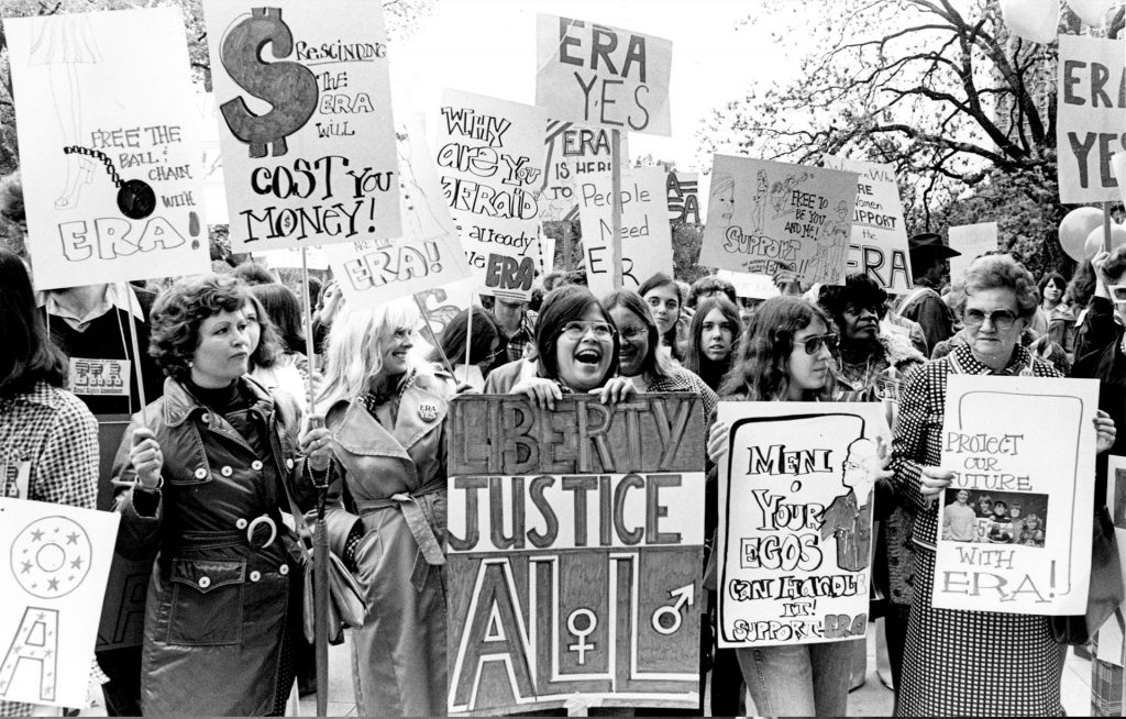 "Women protest in support of the Equal Rights Amendment at the Texas Capitol, April 1975. [Center] Martha Cotera holds ""Liberty, Justice, All"" sign."
