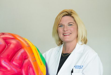 Portrait of Dr. Kimberly Monday standing next to a colorful plastic model of a brain.