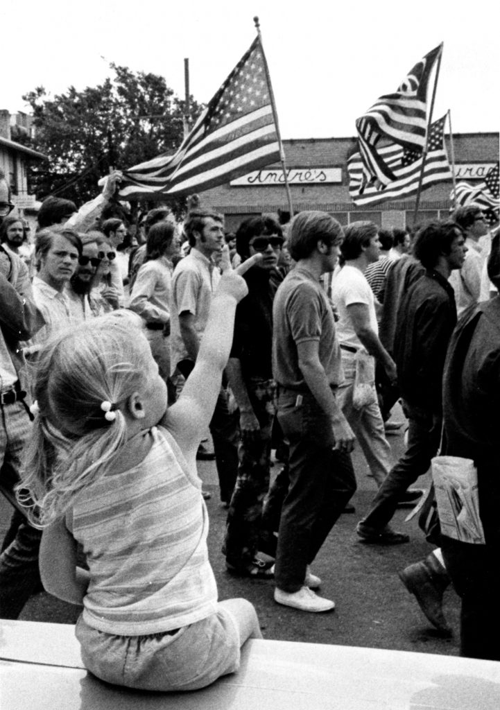 A little girl offering a peace sign to anti-Vietnam War demonstrators during a march in Austin, circa 1968-1972.
