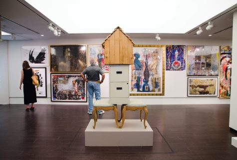 "Photo artwork displayed in the Christian-Green Gallery. The piece of artwork in the foreground, titled ""The Book I Will Never Write,"" is two back-facing chairs with a filing cabinet and large birdhouse-like structure on top. Various large-scale paintings can be seen in the background with people looking at them."