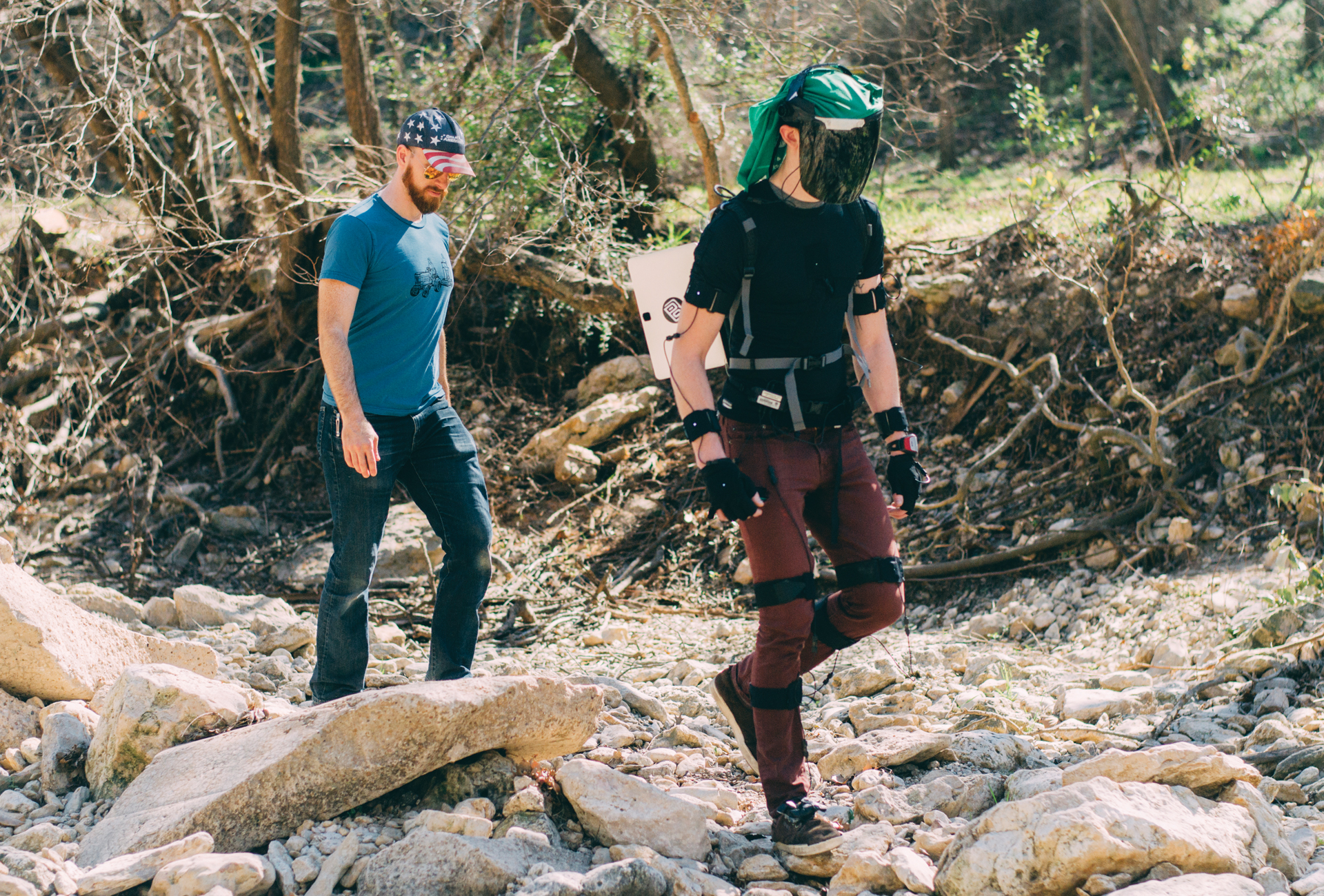 "Jonathan Matthis, a postdoctoral researcher in the Center for Perceptual Systems, observes a research participant in ""medium terrain"" conditions using a motion capture suit, mobile eye tracker and transparent infrared-blocking face shield. Two men walk along a rocky creek bed."