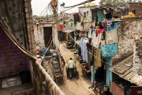 Photo from a balcony in Safeda Basti, India. The street scene below appears dirty and is crowded with laundry hanging from clotheslines while a lone man pushes a banana cart. To the immediate left, we see an open-air squat toilet overlooking a balcony.