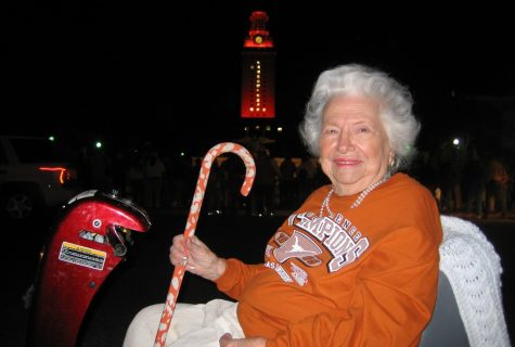 Liz Carpenter in burnt orange champions shirt with the Tower lit orange in background.