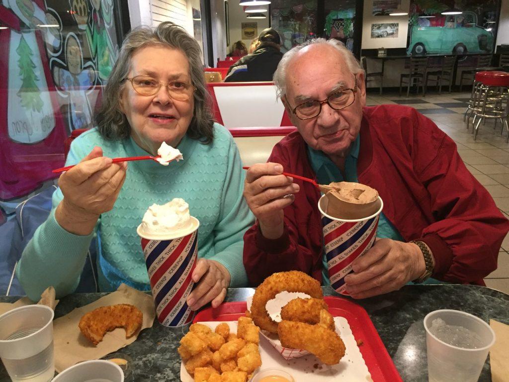 Couple eats large milkshakes.