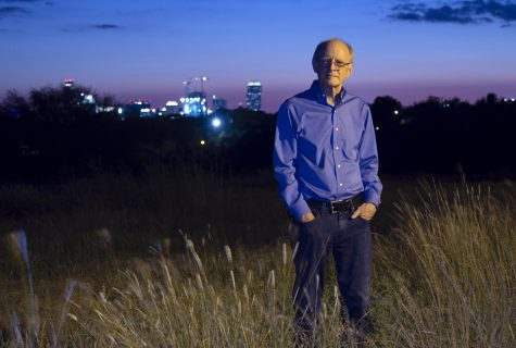 Jamie Pennebaker stands in a field at sunset with cityscape in background.