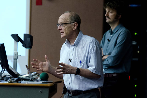 Jamie Pennebaker speaking at class lectern with Sam Gosling in background.