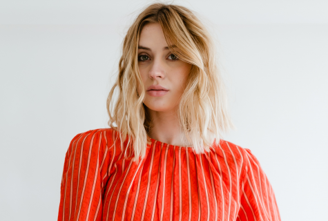 Anna Cash wears a striped red shirt and looks into the camera with a serious expression on her face.