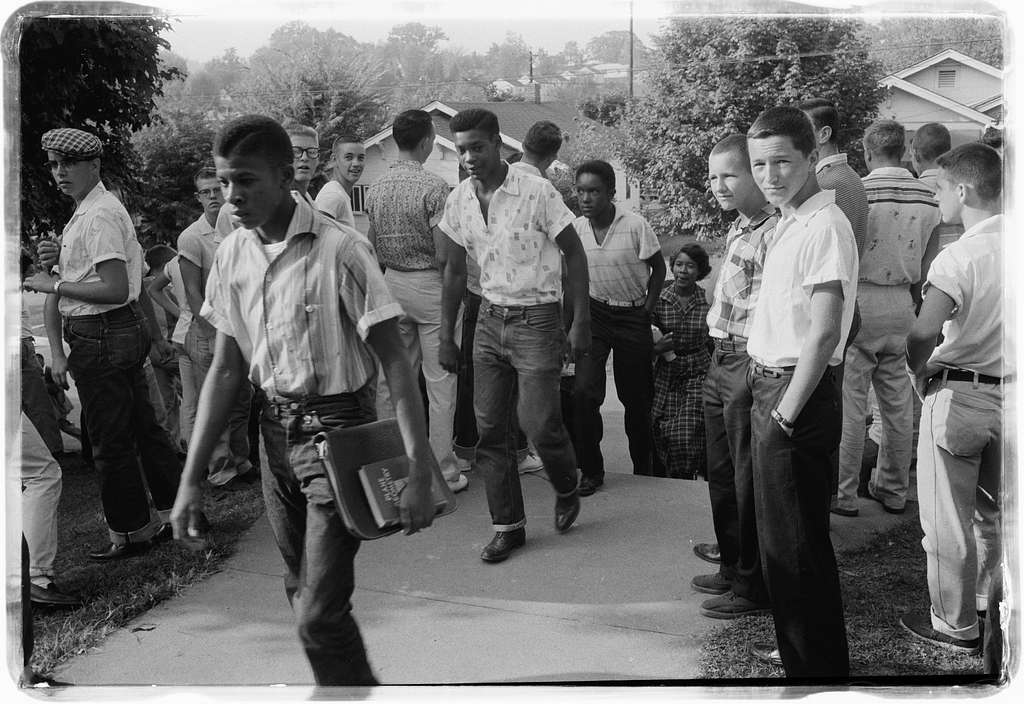 Photograph shows a line of African American boys walking through a crowd of white boys during a period of violence related to school integration.