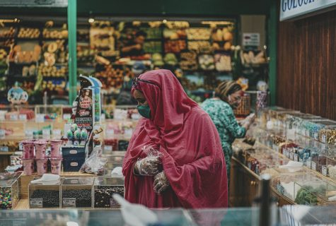 Woman with masks and gloves in candy shop