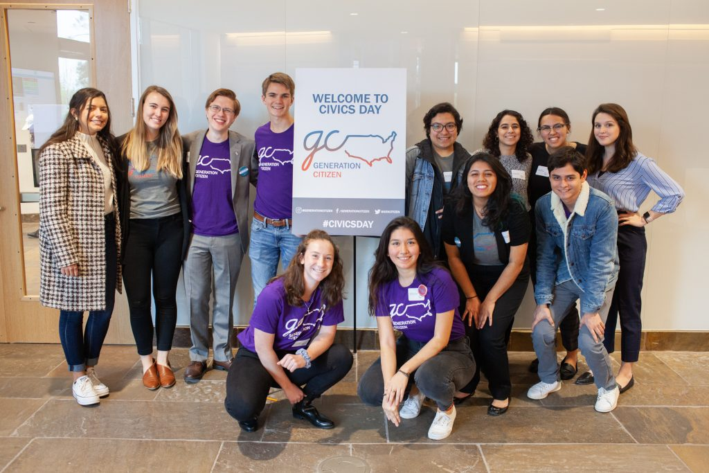 A group shot of Generation Citizen volunteers including Rodriguez. There is a sign with the organization's logo and the words 'Welcome to Civics Day.'
