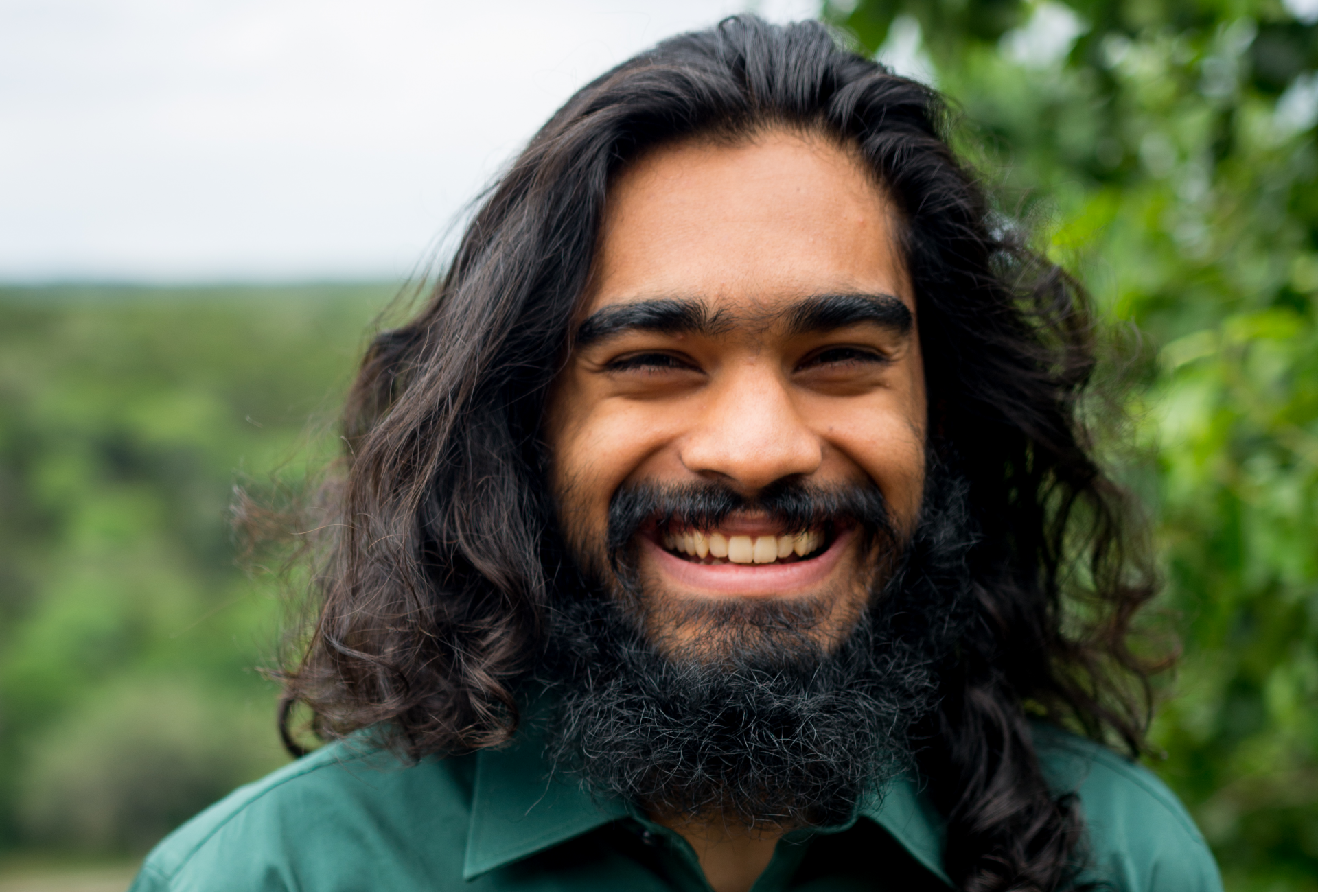 A portrait of Akash Thakkar standing outside and smiling widely with greenery in the background.