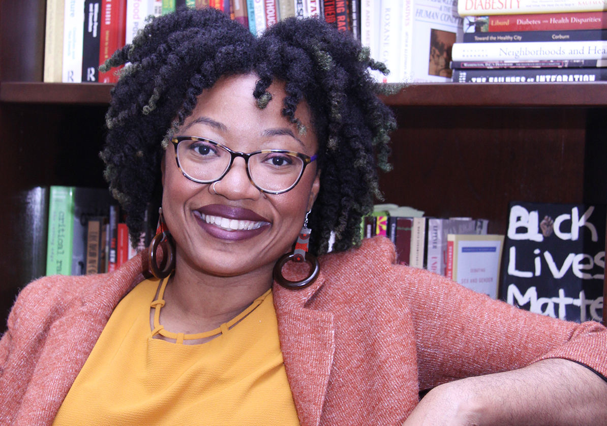 Ashanté Reese sits in front of a full book shelf. She is smiling widely and wearing a red blazer and light orange blouse.