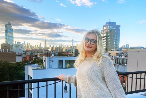Hannah Hayes stands at a railing as the sun sets over the New York City skyline.